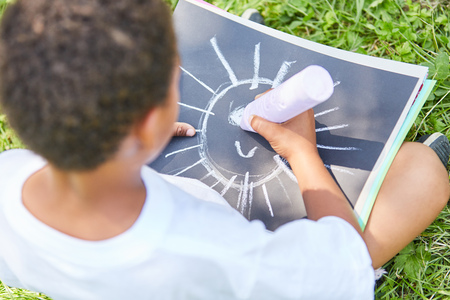 Boy in kindergarten paints the picture of a sun on a sheet of paper with chalk
