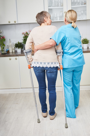 Nursing service for senior woman with crutches Imagens