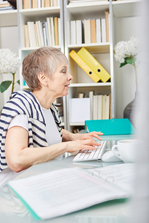 Woman as senior citizen writing and working with computer