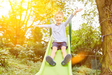 Boy while slipping on a slide in the garden in summer