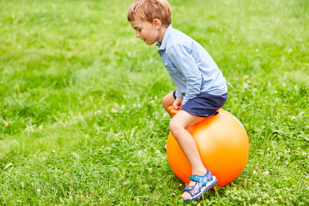 Happy boy is jumping on a hopping ball in the park in summer