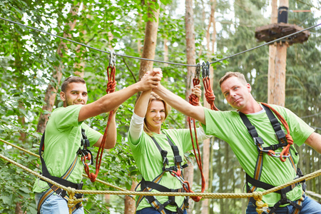 Proud team in the high ropes course congratulates for the successful cooperation