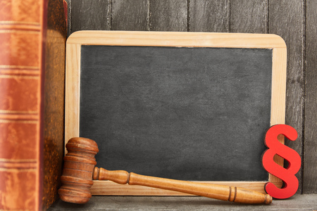 Training as a lawyer with empty chalkboard and law symbols such as paragraph and judge gavel Фото со стока