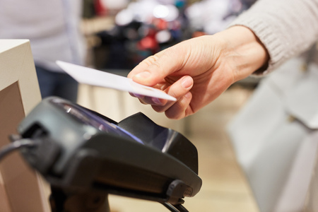 Customer pays with NFC credit card at the card terminal in the mall