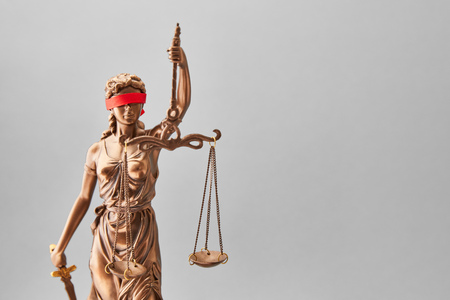 Justitia statue in bronze with red blindfold as justice concept Foto de archivo