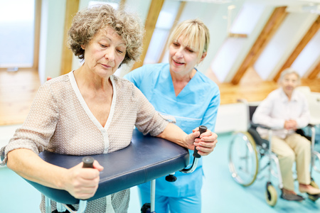 Therapist helps senior citizen with walker learning to walk in rehab clinic