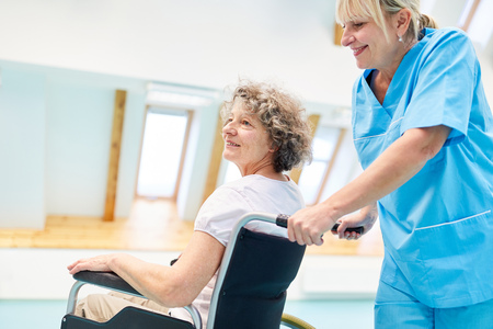 Caregiver cares for a senior woman in a wheelchair in physiotherapy Stockfoto