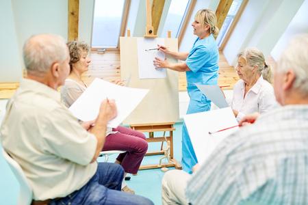 Aînés atteints de démence au cours de dessin encadré par un thérapeute en maison de retraite