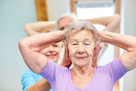 Trainer pays attention to proper execution of physiotherapy exercise with senior citizen