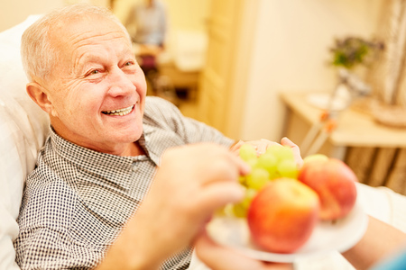 Nursing help old man fresh fruit in nursing home or at home 版權商用圖片