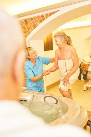 Caregiver helps senior woman while bathing in the hot tub of the senior residence Zdjęcie Seryjne