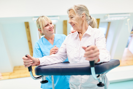 Senior with walker learning to go rehabilitation supervised by a therapist Stock Photo