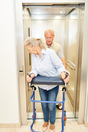 Senior with rollator and senior man in an elevator in a nursing home