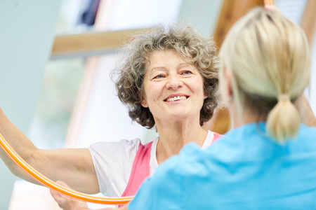 Happy senior woman at the physiotherapy with a hoop