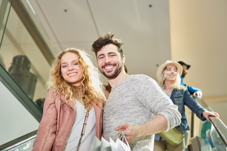 Happy young couple shopping together in shopping mall