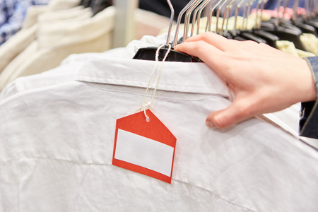 Blank price tag on clothing with hand in retail