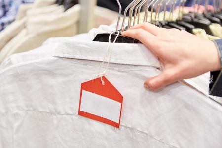 Leeres Preisschild auf Kleidung mit Hand im Einzelhandel