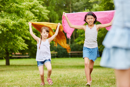 Girls running and playing with cloth in the park