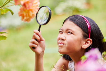 Girl with magnifying glass explores and observes flowers in nature Banco de Imagens