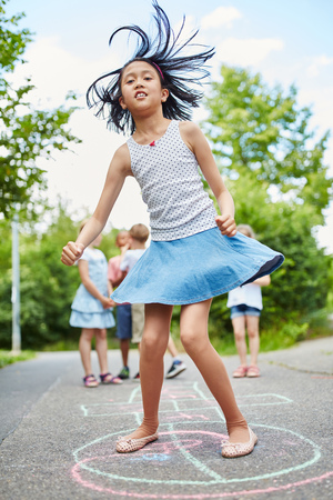 Active girl jumping during hopscotch game for fun Stockfoto