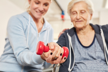 Physiotherapist helps elderly woman with healthy dumbbell training in rehab