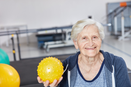 Happy senior woman with ball in occupational therapy at the fitness center