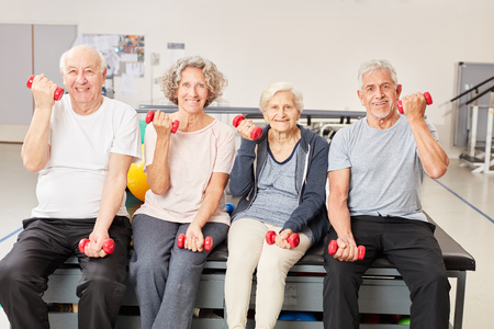 Senior group rehabilitation training with dumbbells for strength and mobility