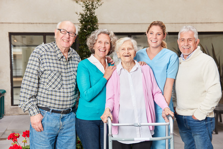 Group of seniors as friends laugh happily with geriatric nurse in retirement home