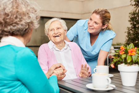 Senior women laugh and have fun in retirement home drinking coffee