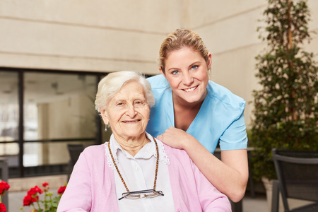 Nursing assistance and senior woman together in nursing home or senior residence