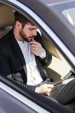 Businessman with tablet computer sits thoughtfully in the car on a business trip Stock Photo