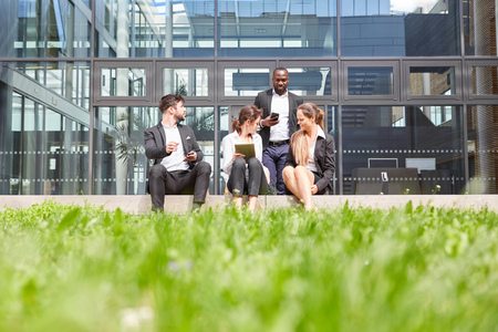 Group of business people pauses and sits in front of the office building in summer Reklamní fotografie