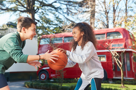 Two teenagers are playing basketball at summer camp together in competition