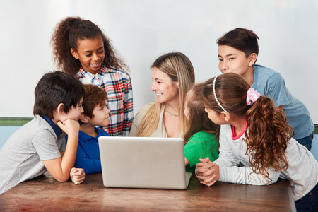 Woman as a teacher and a group of students together at the laptop computer