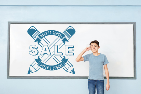 Student stands at whiteboard promoting Back to School Sale with Discount Stock Photo
