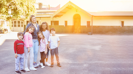 Happy group of children in elementary school is standing with the teacher in the schoolyard Stockfoto - 115806990