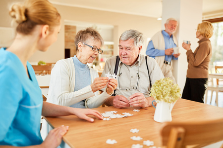 Seniors playing puzzle in their spare time in retirement home or assisted living