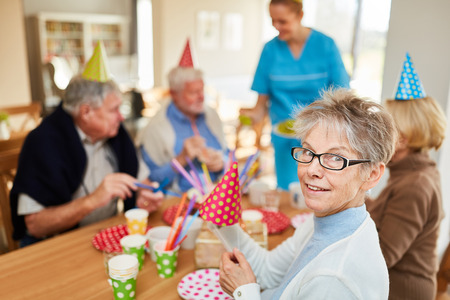 Happy seniors at a birthday party in retirement home at the coffee table