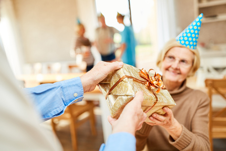Senior woman is surprised with a gift at her birthday party in retirement home Banco de Imagens - 115807218