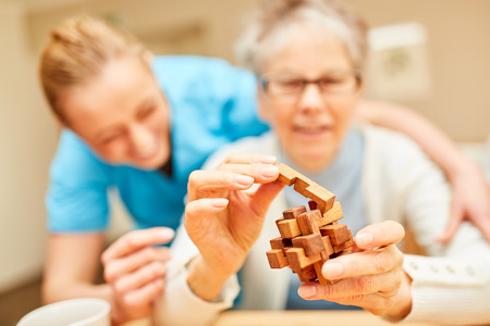 Senior woman with dementia plays with a wooden puzzle as employment in nursing home Banque d'images - 115807021