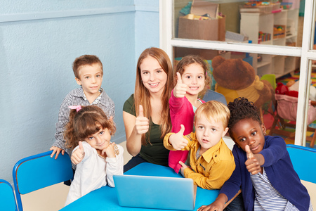 Teacher and children with thumbs up in computer course of preschool or elementary school Stockfoto