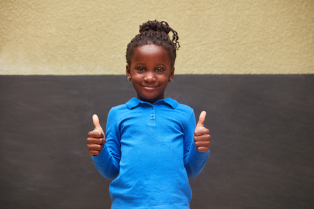 African girl in front of a blackboard holds both thumbs up as a sign of success