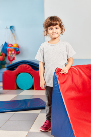 Happy girl is standing in the gym in preschool or kindergarten Stock Photo