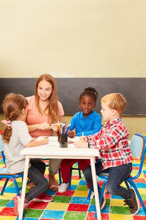 Groupe d'enfants multiculturels et éducateur en peignant ensemble à la maternelle