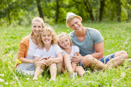 Happy family is sitting together in summer on a meadow