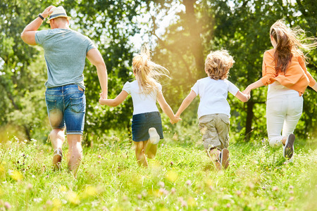 Active family and children run across a meadow in summer