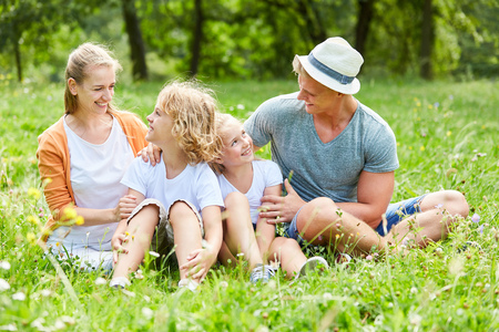 Happy family and children are sitting together on summer meadow Stok Fotoğraf