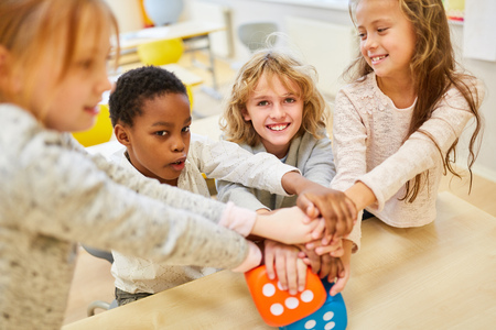 Multicultural children as friends and students stack hands for integration