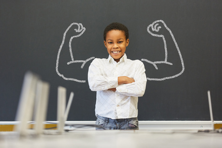 African kid in front of blackboard with muscles Stock Photo