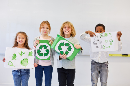Student team of elementary school with drawings on ecology and recycling project